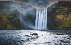 Majestic nature of Iceland. Impressively View on Skogafoss Waterfall with colorful sky glowing sunlight, during sunrise. Skogafoss the most famous place of Iceland. creative artistic image. postcard