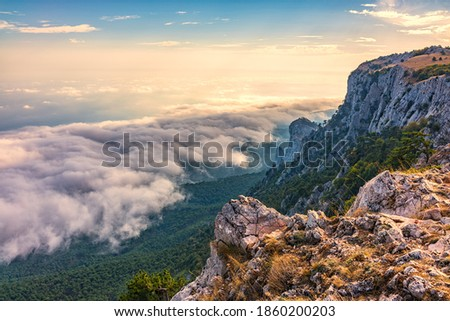 Majestic orange sunset over the rocky mountains and the valley in fog and clouds. Creamy fog covered the mountain valley in sunset light. Misty sunset over Crimea Mountains. Ai-Petri, Crimea. Stock foto ©