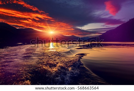 majestic overcast landscape . red clouds glowing in sunlight. at the river. Mountain lake at dark. creative image. instagram filter #568663564