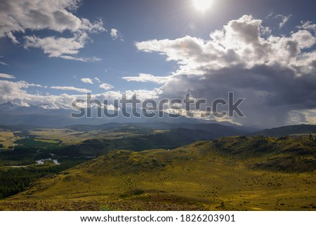 Majestic panorama of mountain plain on the background of snow-covered ridge before thunderstorm. Sun