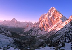 Majestic peaks at sunrise; magical morning in a mountain valley; cloudless sky, first rays of the sun, the beginning of a perfect day