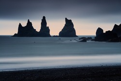 Majestic rocky needles from sea, Reynisdrangar, close to Vik Iceland. Dramatic sunset sky and with long exposure motion blurred waves.