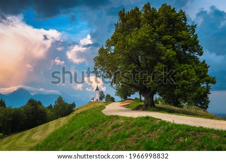 Majestic scenery with cute church on the mountain ridge. Sunset scenery and famous charming Saint Primoz church with mountains in background, Jamnik village, Slovenia, Europe Zdjęcia stock ©