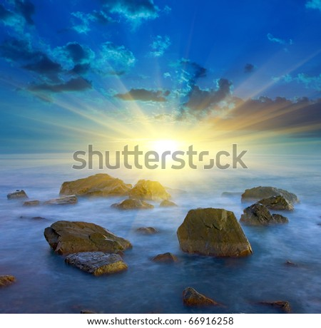Majestic sunset over stone in sea
