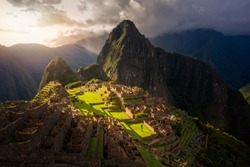 Majestic sunset over the Machu Picchu / Huayna Picchu mountain with Incan sacred city ruins. Beautiful landscape.