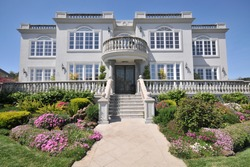 Majestic two story mansion with shrubs in yard. Blue sky. Lots of windows and railings.