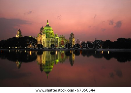 Majestic Victoria Memorial building reflected across lake at sunset