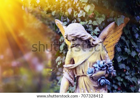 Majestic view of statue of golden angel illuminated by sunlight against a background of dark foliage. Dramatic unusual scene. Beauty statue.