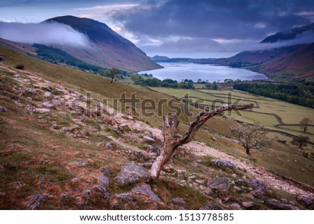 Majestic view on scenic mountain valley with lake before sunrise.Clouds rolling over hills in background and tree trunk in foreground.Idyllic morning scenery of English Lake District.