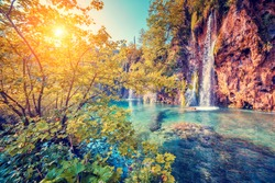 Majestic view on turquoise water and sunny beams in the Plitvice Lakes National Park. Wood glowing by sunlight. Croatia. Europe. Dramatic unusual scene. Beauty world. Retro and vintage toning effect.