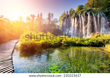 Majestic view on waterfall with turquoise water and sunny beams in Plitvice Lakes National Park Forest glowing by sunlight Croatia Europe Dramatic morning scene Beauty world Instagram effect