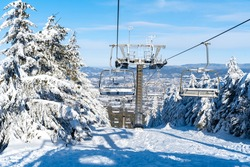 Majestic winter landscape with ski lift and trees covered by ice and snow.  Beautiful sunny winter day in mountains.