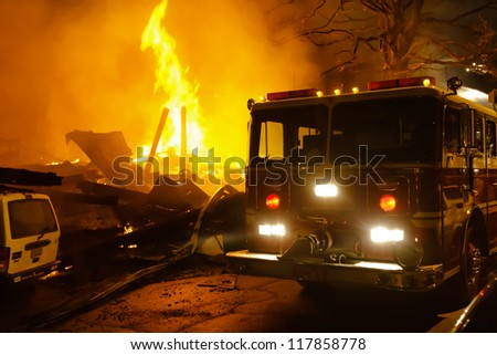 Major building fire with fire engine, smoke and heavy flame.