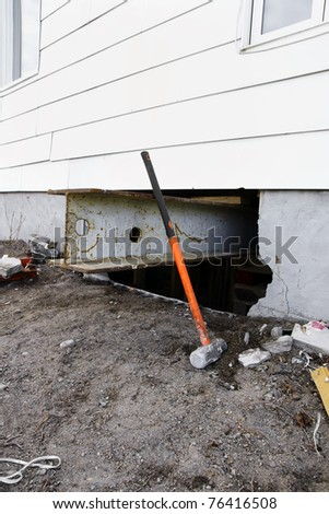 Major reno: sledgehammer against strong steel beam inserted for support to lift and old house with white siding to change the damaged concrete block foundation.