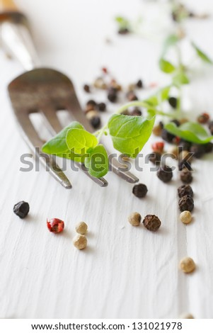 Majoram and a fork, assorted peppercorns on a white wooden table useful as a herb concept background