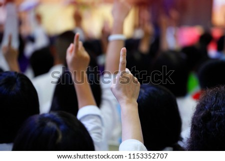 Majority of volunteer people reacting to the question by raising their index finger together as teamwork for unity and unanimous agreement and collaboration in the classroom