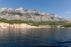 Makarska in Dalmatia, Croatia. View from the sea on a sunny day in the summer and a blue sky. A idyllic place with beaches and the Biokovo moutain. Holiday destination at the Mediterranean coast.
