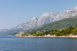 Makarska Riviera in Dalmatia, Croatia. View from the sea on a sunny day in the summer and a blue sky. A famous place with beaches and the Biokovo mountain. Holiday destination, Mediterranean coast