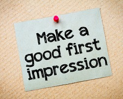 Make a first good impression Message. Recycled paper note pinned on cork board. Concept Image