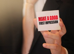 Make a good first impression on a card Businessman holding. Motivation and personal coaching concept.