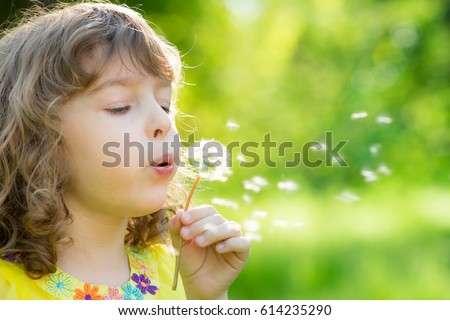Make a wish! Happy child blowing dandelion flower outdoors. Girl having fun in spring park. Blurred green background. Dream and imagination concept
