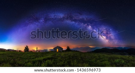 Make a wish - Meteor shower during summer with full arc of milky way and falling stars, perseids. Beautiful Universe. Small chapel in foreground. Space background.