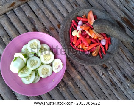 make chili sauce or Indonesian people call it sambel, using a smoothing tool made of stone, chili sauce is made of shallot,garlic,red chili,tomato and there are fresh cucumber slices as a complement Foto stock ©