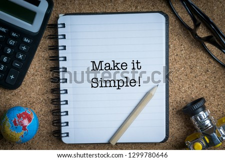 MAKE IT SIMPLE inscription written on book with globe,eyeglasses, calculator, camera, pencil and vase on wooden background with selective focus and crop fragment. Business and education concept Stock fotó ©