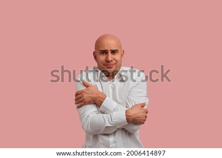 Make it warmer, please. Frozen bald man with bristle trembles from cold in office. Dissatisfied with the cold from the air conditioner. Dressed in white shirt. Isolated over pink background Stock photo ©