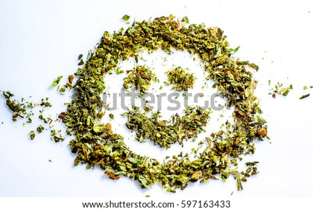 make me smile with cannabis green grass. smiled smile made by dry cut green cannabis before using. Marijuana Bud Cannabis Close Up On white background #597163433