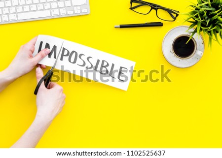 Make the impossible possible. Cutting the part im of written word impossible by sciccors. Office desk. Yellow background top view copy space