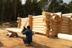 Make the Layout when Building a Wooden Block. Layout and Preparation of New Wooden Logs for the Assembly of the Structure. Assembling a Wooden Log House on a Construction Site.