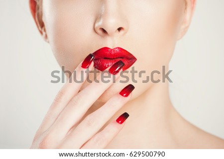 Make up and manicure set. macro cropped image of beautiful gradient of red black manicure and lipstick isolated on white background. #629500790