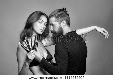 make-up artist and his model. young couple of sexy woman with pretty face and long brunette hair in black bra on body and handsome bearded man visagiste with fashionable makeup brush in studio on grey #1114959902