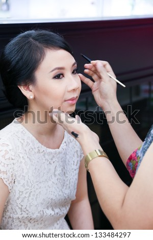 Make-up artist applying cosmetics on a beautiful young asian lady