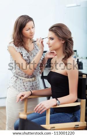 Make-up artist applying eyebrow make-up, selective focus on model