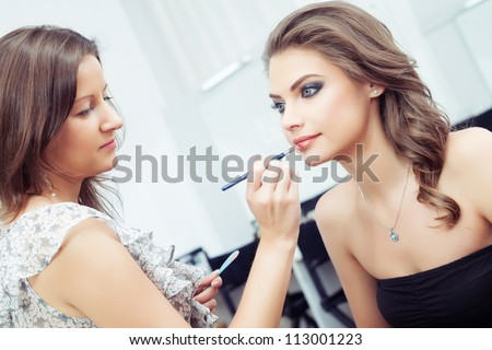 Make-up artist applying lipstick with a brush on model's lips