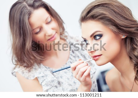 Make-up artist applying lipstick with a brush on model's lips, close-up