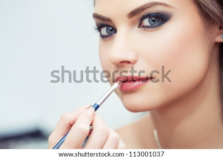 Make-up artist applying lipstick with a brush on model's lips, close-up, model looking at camera