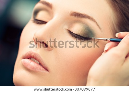 Make-up artist applying liquid eyeliner on model's eyes, close up