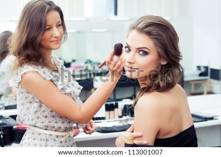 Make-up artist applying powder with a brush on model\'s cheeks, selective focus on model looking at camera