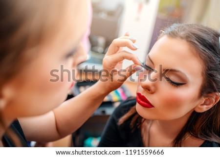Make-up artist applying the false eyelashes to model. Close-up.
