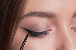 Make-up artist brush black eyeliner on the face of the woman. Young beautiful woman applying make-up by make-up artist