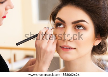 make-up artist doing make-up beautiful girl in the salon, beauty concept and style #558062626