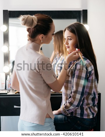 make up artist doing professional make up of young woman #420610141