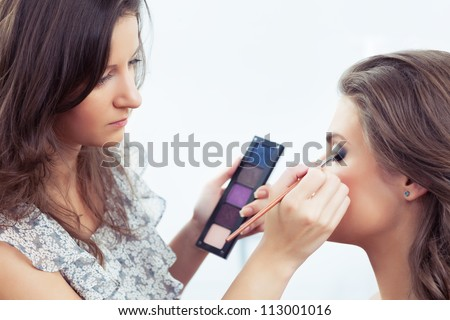 Make-up artist holding eye shadow palette and applying make-up, selective focus on model's eye