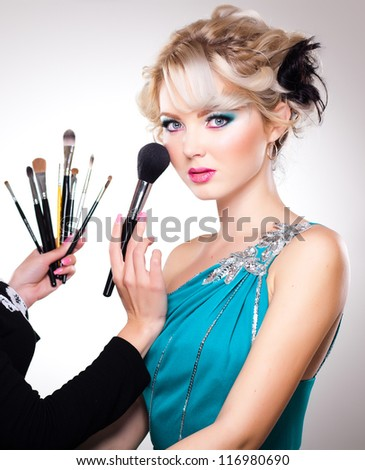 Make-up artist in action on beautiful doll face - blue eyes and blond hair