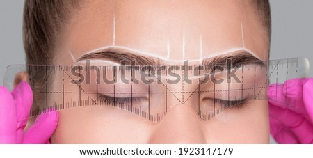 Make-up artist makes markings with white pencil for eyebrow and paints eyebrows. Professional makeup and facial care. Foto stock ©