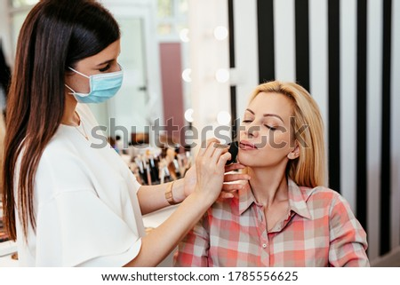 Make up artist with face protective mask applying professional make up of beautiful middle age blonde woman. Coronavirus pandemic lifestyle. Photo stock ©