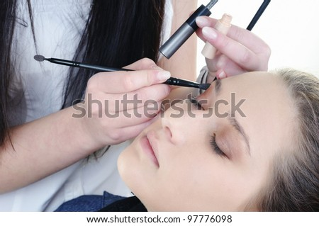 Make-up artist woman fashion model apply eyeshadow with brush